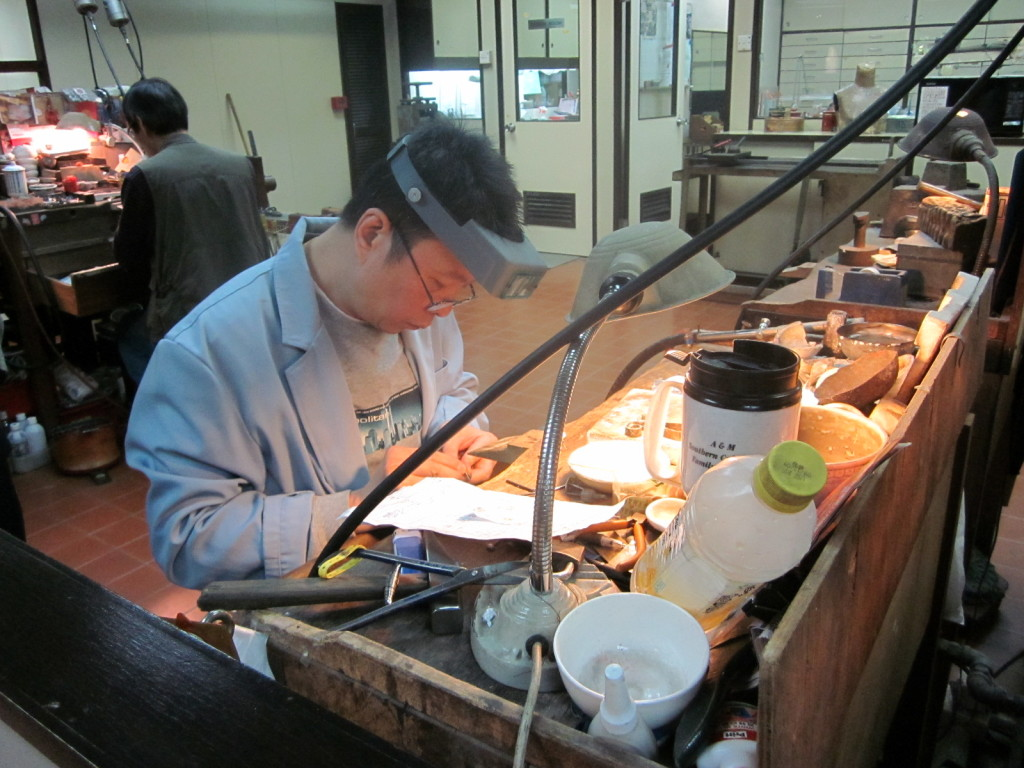 Worker at a jade factory setting a ring.