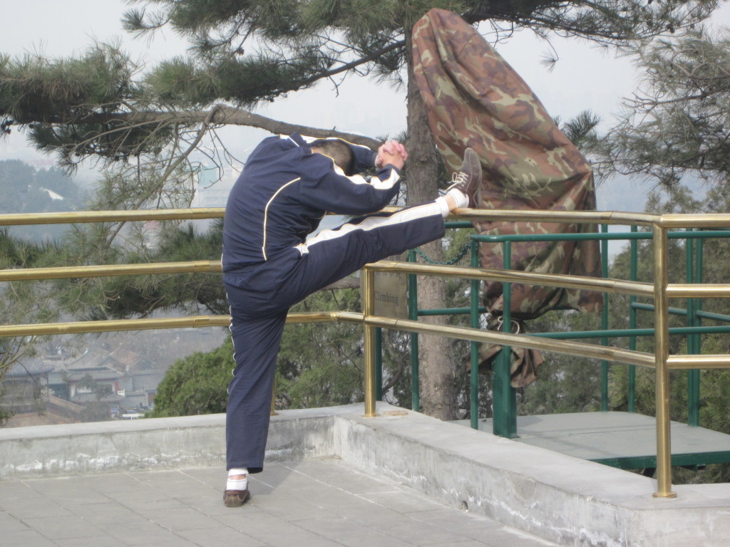 Man stretching as part of his morning Tai chi routine,