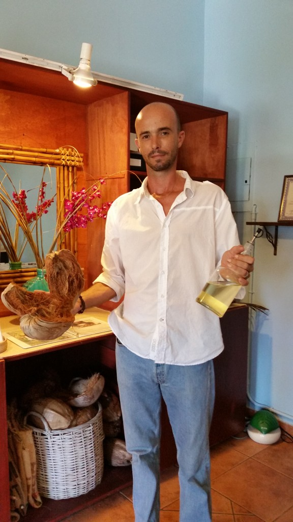 Kristof, the store owner showing the coconut husk and the raw oil.