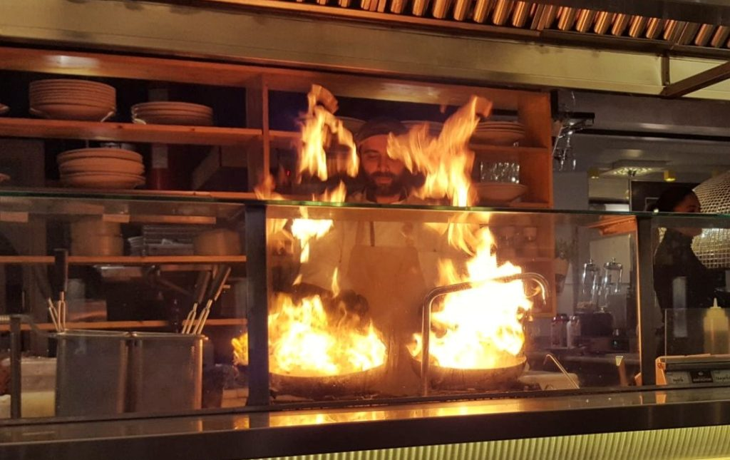Chef over fire in open kitchen_Athens_Greece
