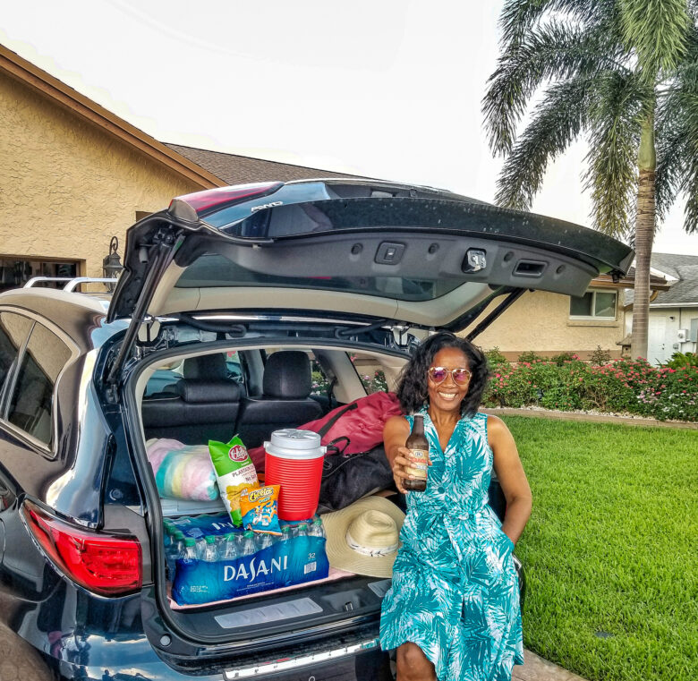 Black woman leaning against trunk of SUV packed or a long road trip